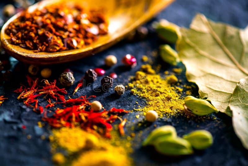 Spezie Varie spezie indiane sulla tavola di pietra nera Spezia ed erbe sul fondo dell'ardesia fotografie stock libere da diritti