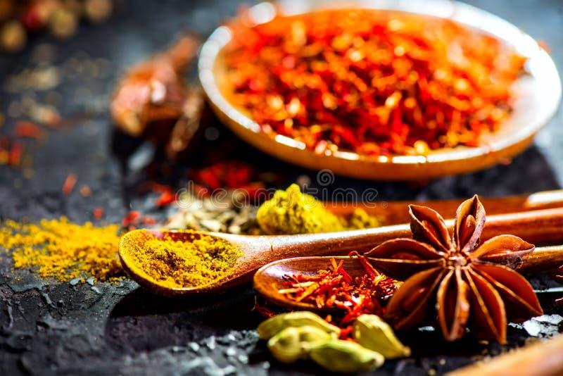 Spezie Varie spezie indiane sulla tavola di pietra nera Spezia ed erbe sul fondo dell'ardesia fotografie stock
