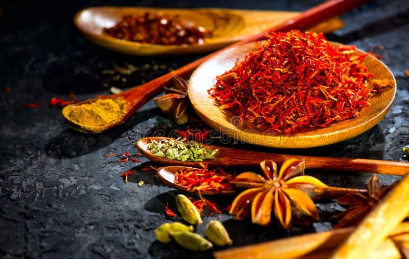 Spezie Varie spezie indiane sulla tavola di pietra nera Spezia ed erbe sul fondo dell'ardesia fotografia stock libera da diritti