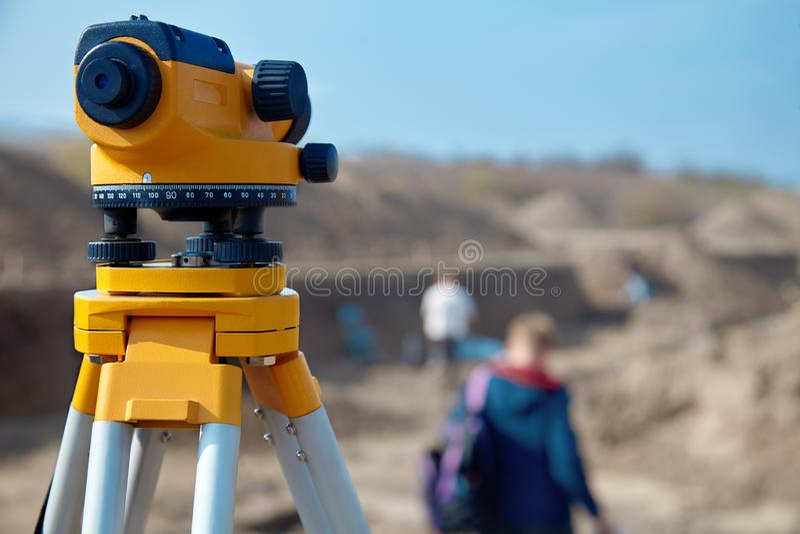 Spezielle Geräteebene für Feldmessererbauer, Geodäsieausrüstungsabschluß oben vor einem Fundament mit Leuten auf unscharfem backg stockfoto