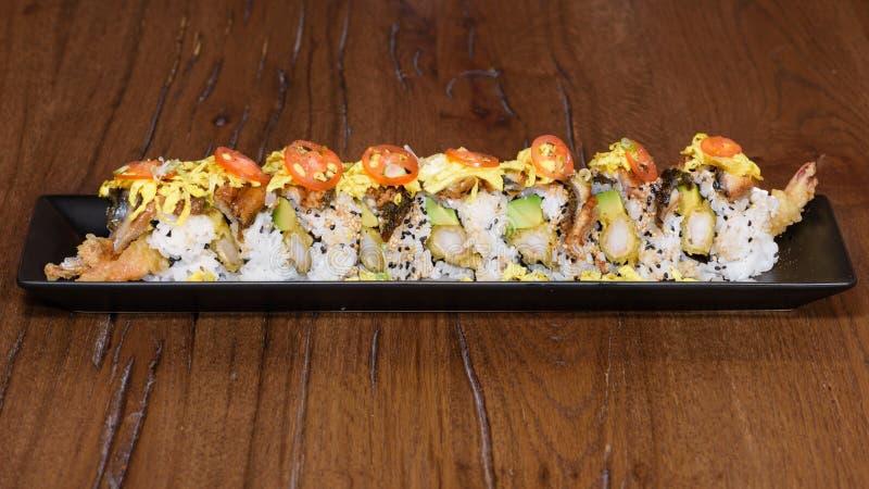Spezielle Sushirolle mit gebratenem Aal, Garnele im Tempura, Kirschtomaten, Mayonnaise, Omelett und indischem Sesam lizenzfreie stockfotos