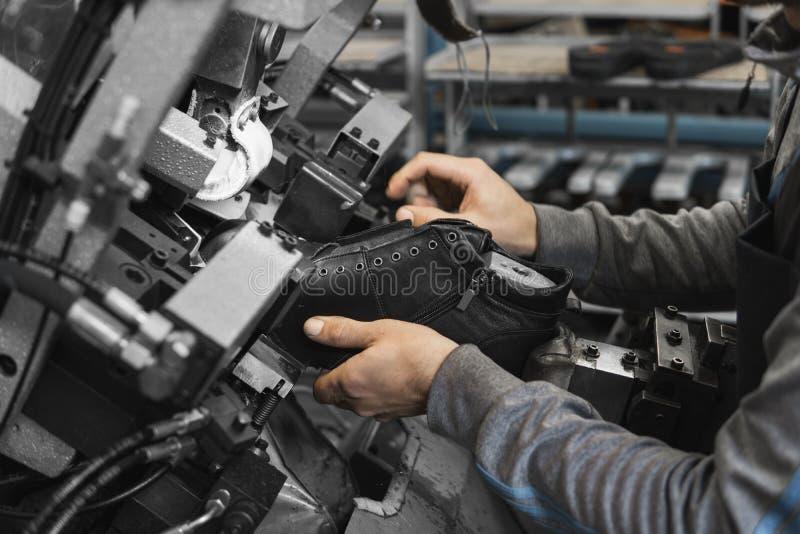 Spezielle Werkzeugmaschine des Manngebrauches für die Herstellung von Schuhen Der Förderer auf einer Schuhfabrik mit Schuh und So stockbild