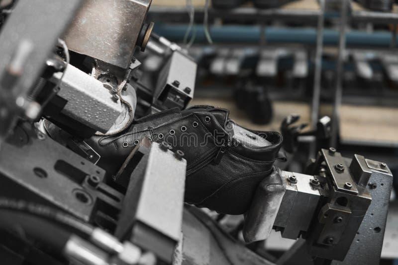 Spezielle Werkzeugmaschine des Manngebrauches für die Herstellung von Schuhen Der Förderer auf einer Schuhfabrik mit Schuh und So stockfoto
