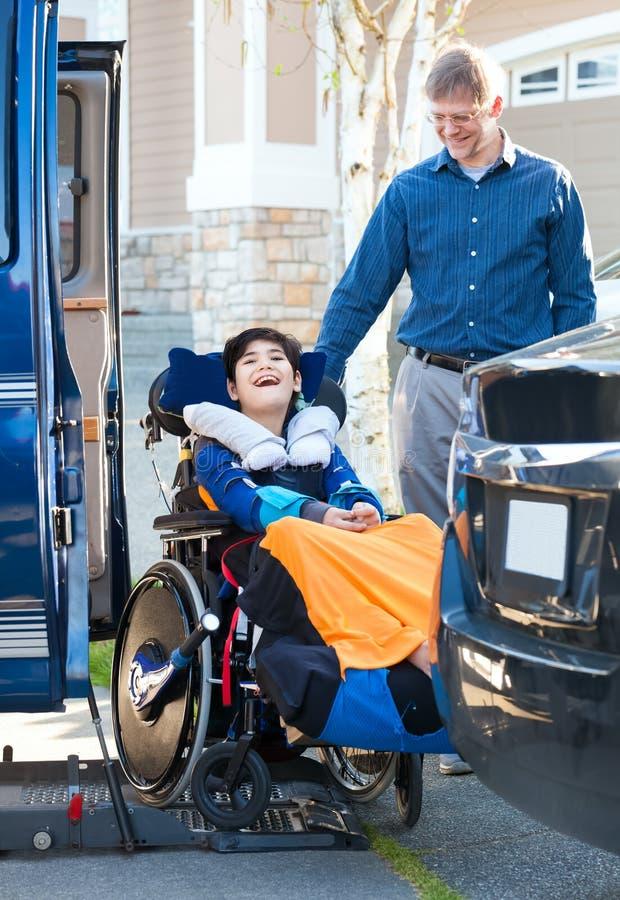 Spezieller Bedarfsjunge im Rollstuhl auf Fahrzeughandikapaufzug stockbilder