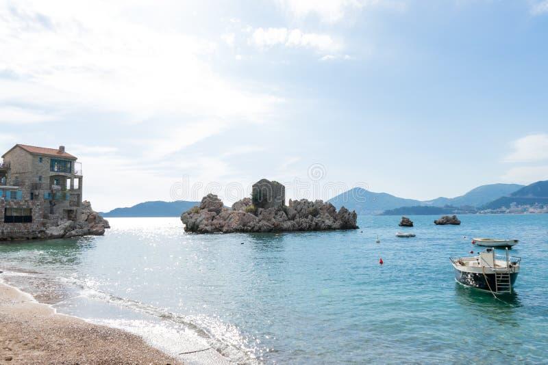 Spezieller unterschiedlicher Felsen im adriatischen Meer in einem kleinen Küstendorf in Budva Kleine Boote im Strand im blauen Wa lizenzfreie stockfotografie