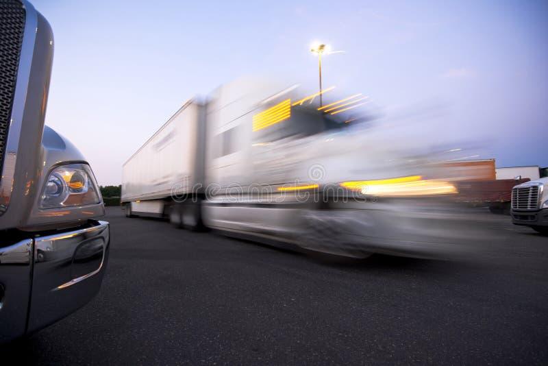 Spezzetti i camion moderni su trakstope contro il camion commovente con He immagine stock libera da diritti