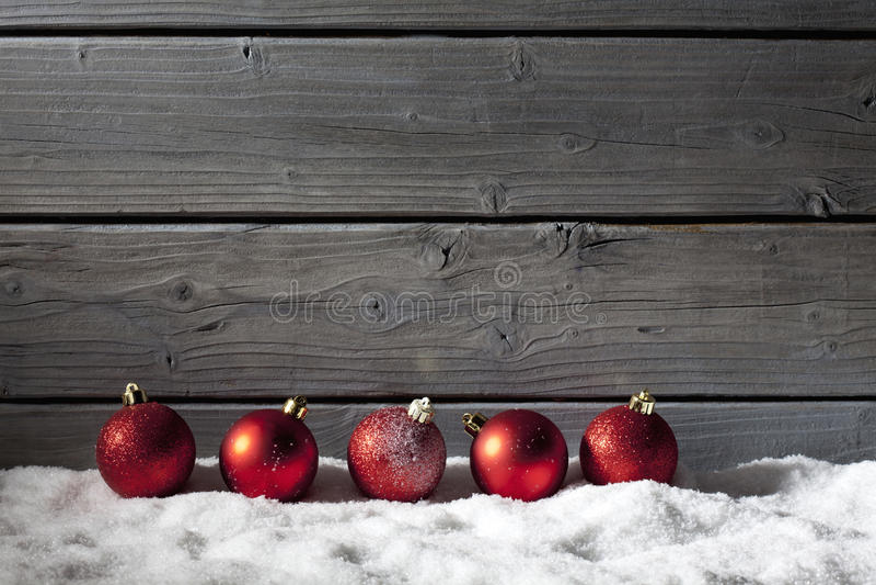 Sphères rouges de Noël sur la pile de la neige contre le mur en bois photographie stock libre de droits