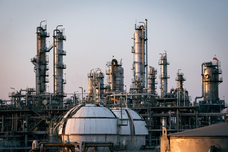 Sphere gas storage tank and chimney petrochemical plant på morgonen royaltyfri bild