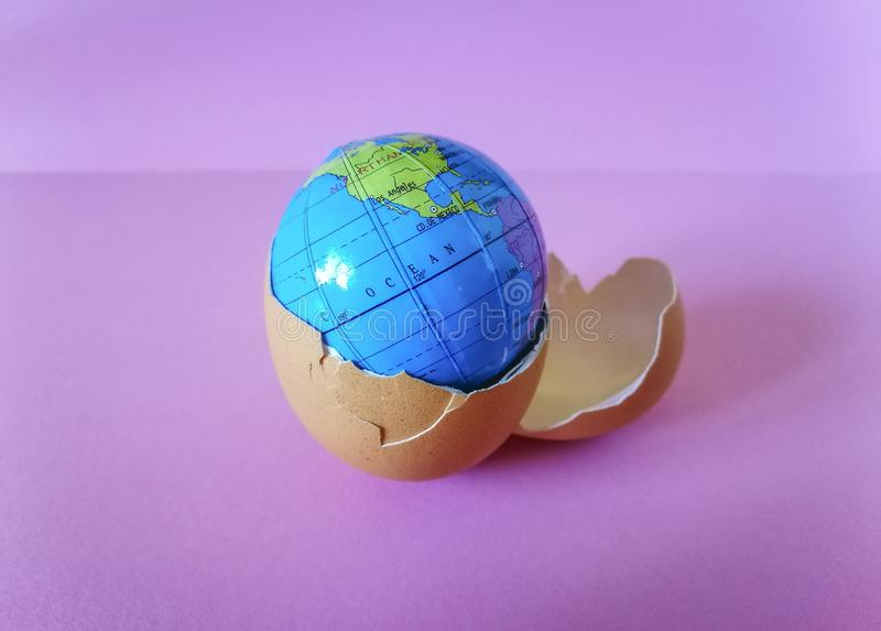 Spherical Earth map  inside egg shell. Spherical Earth map placed inside a broken egg shell , on pink background, conceptual image about global stock image