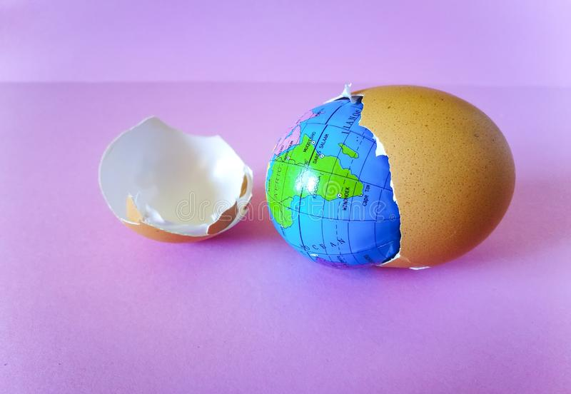 Spherical Earth map  inside egg shell. Spherical Earth map placed inside a broken egg shell , on pink background, conceptual image about global royalty free stock photography