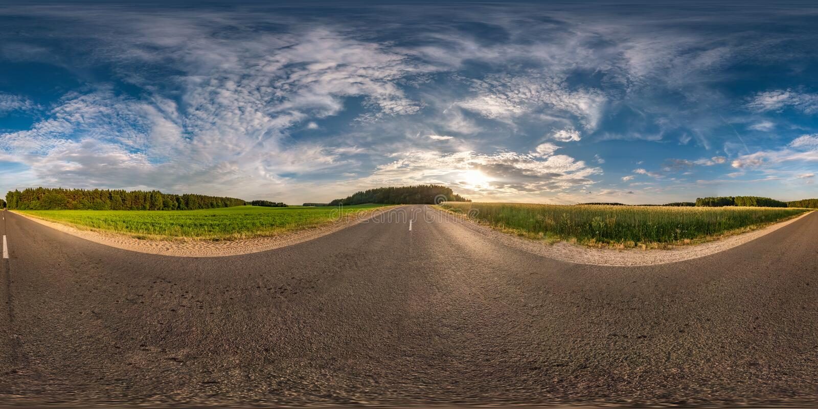 Spherical hdri panorama 360 degrees angle view on asphalt road among fields in summer evening sunset with awesome clouds in royalty free stock photos