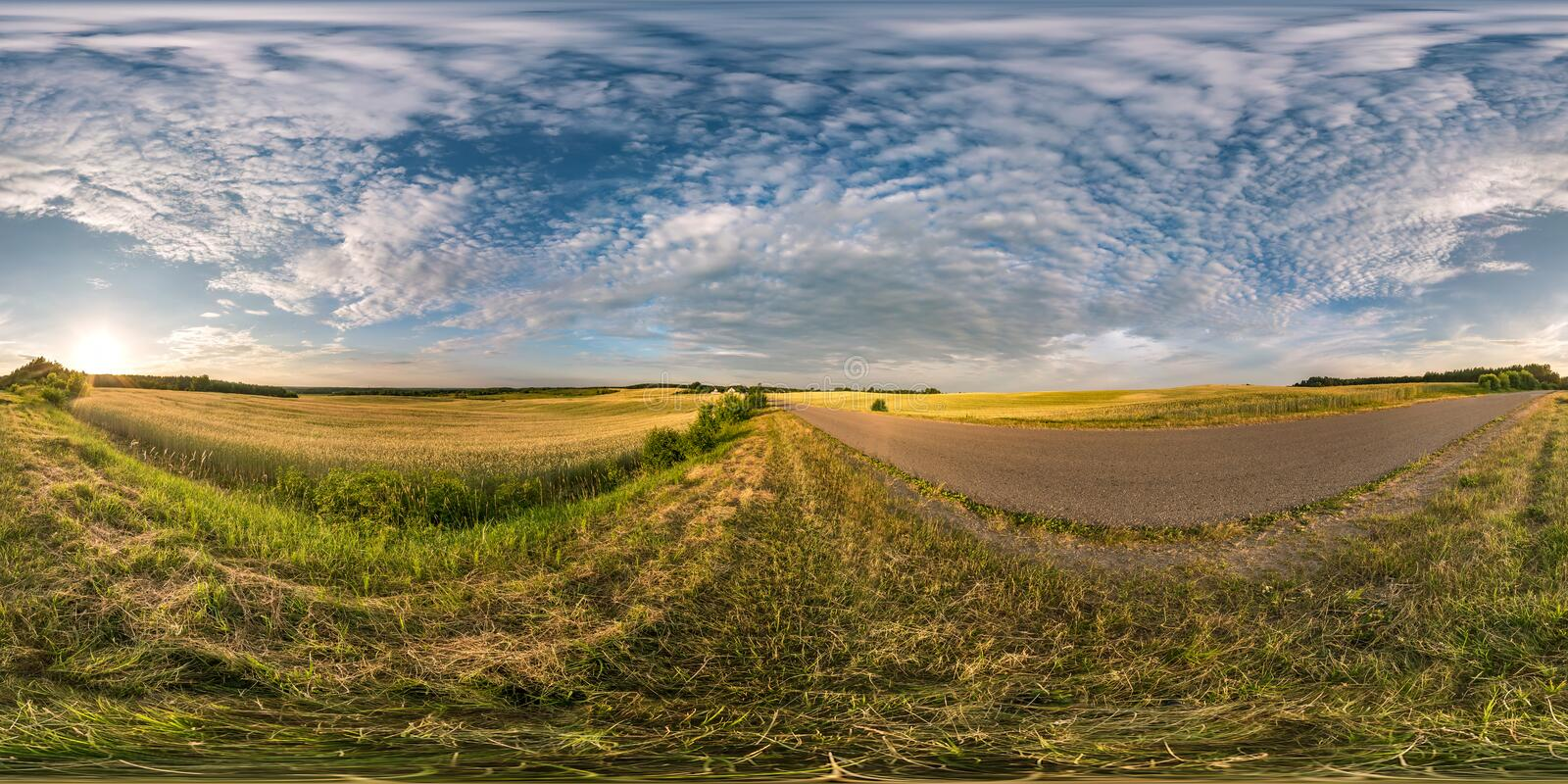 Spherical hdri panorama 360 degrees angle view near asphalt road among fields in summer evening sunset with cirrocumulus clouds in. Equirectangular projection royalty free stock image