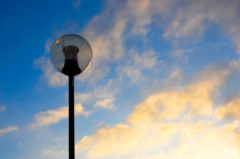 Spherical street lamp against a sunset sky stock photo