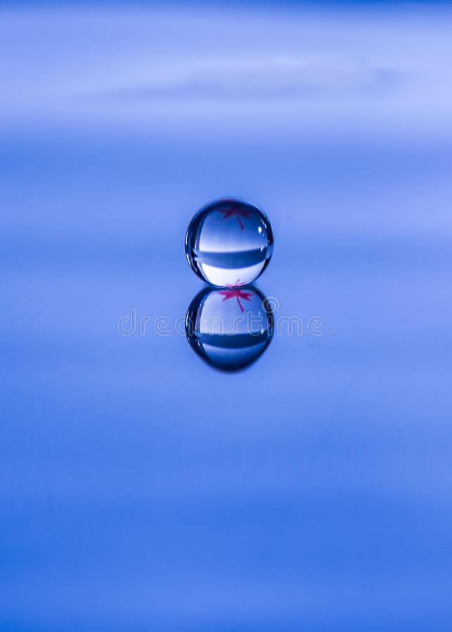 Spherical water droplet reflected. Into a smooth pool stock photo