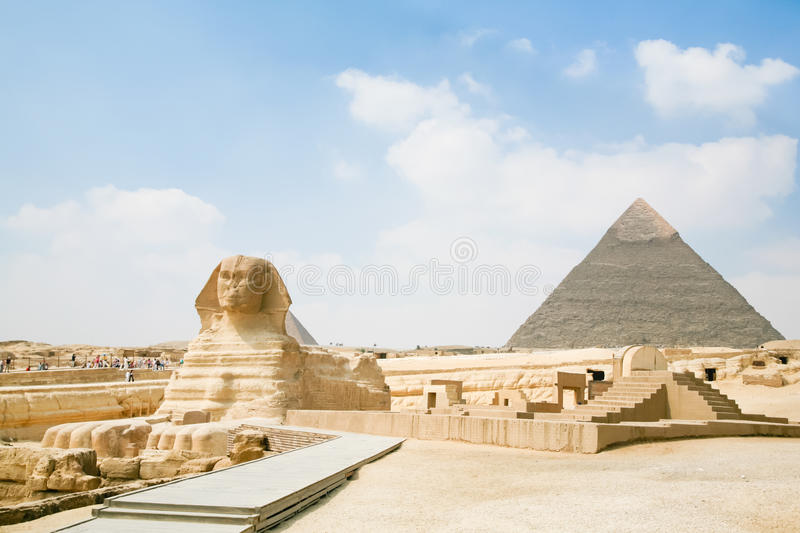 Sphinx and pyramid in Egypt. Landmark of famous Great Sphinx, from century XXVI Before Christ, and behind the Great Pyramid of Khafre, in Giza next to Cairo city stock photography