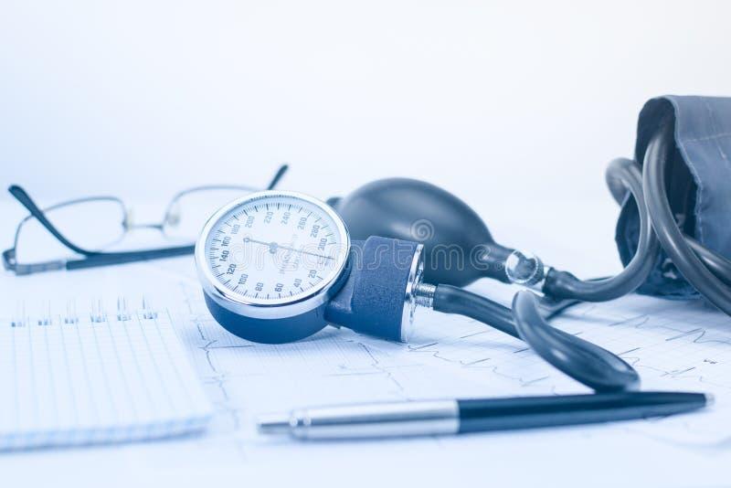 Sphygmomanometer op de werkende lijst van een cardioloog Tonometer, elektrocardiogram en blocnote met pen voor verslagen royalty-vrije stock afbeelding