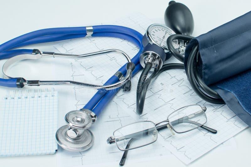 Sphygmomanometer op de werkende lijst van een cardioloog Tonometer, elektrocardiogram en blocnote voor verslagen royalty-vrije stock afbeeldingen