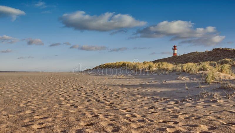Spiaggia abbandonata con il faro dietro le dune di sabbia fotografie stock libere da diritti
