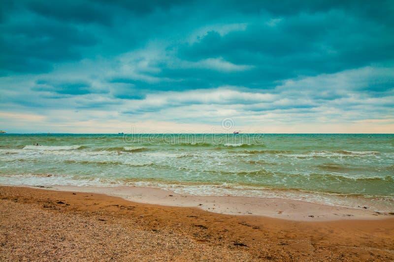 Spiaggia abbandonata, mare con il cielo tempestoso drammatico fotografia stock