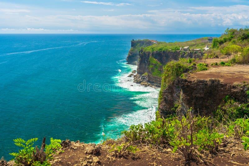 Spiaggia azzurrata con le montagne rocciose e chiara acqua di Oceano Indiano al giorno soleggiato/vista di una scogliera in Bali  immagini stock libere da diritti