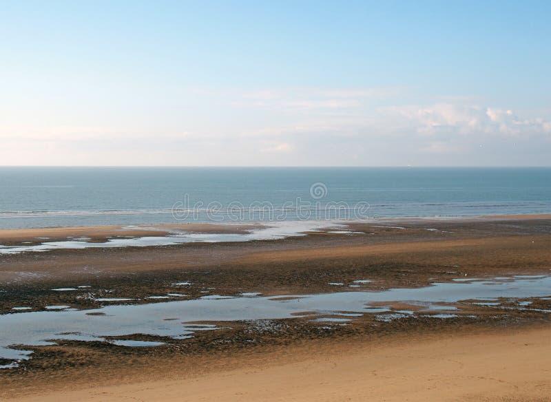Spiaggia a bassa marea con pozze d'acqua accanto a un mare blu e un cielo blu calmo fotografie stock libere da diritti
