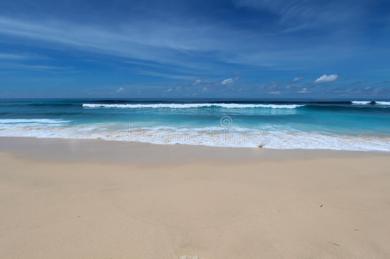 spiaggia blu con la sabbia e le onde bianche nell'area di Bukit, Bali immagine stock libera da diritti