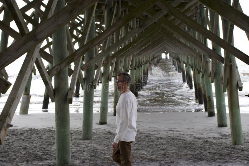 Spiaggia Carolina del Sud di follia, il 17 febbraio 2018 - maschio bianco che cammina sotto il pilastro della spiaggia fotografia stock