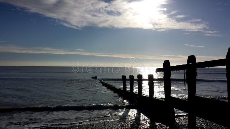 Spiaggia ciottolosa che riflette il sole fotografia stock