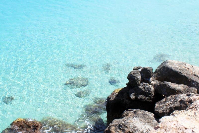 Spiaggia con le pietre e chiara acqua blu immagine stock