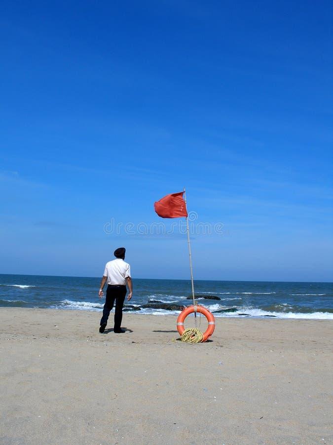 Spiaggia con lifebuoy e l'uomo fotografia stock libera da diritti