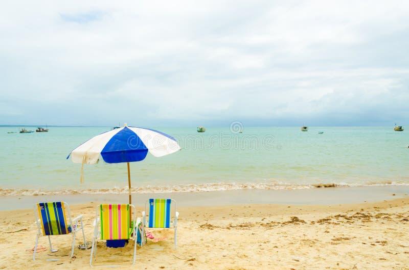 spiaggia con tre sedie di spiaggia variopinte e un ombrello blu e bianco Piccoli frangiflutti nella sabbia immagine stock