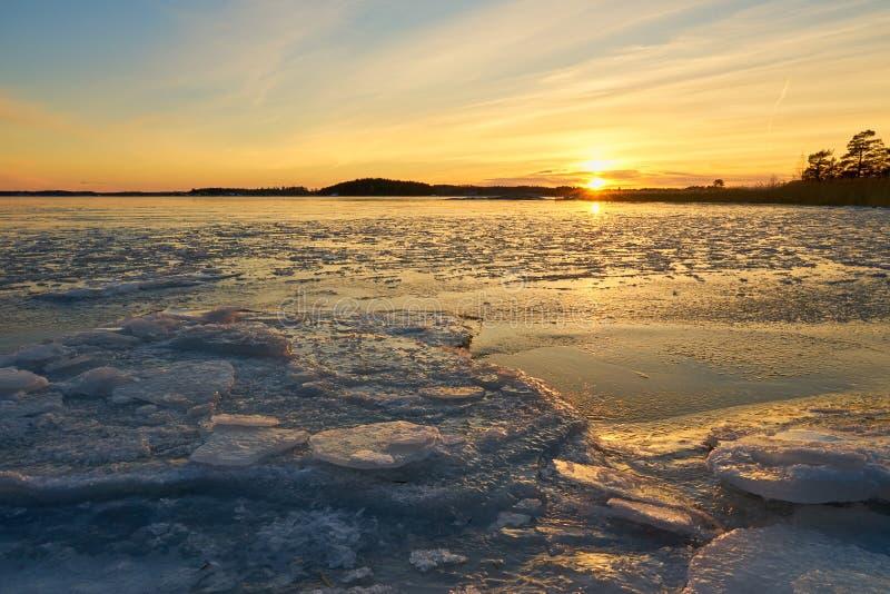 Spiaggia congelata e mare ghiacciato su un tramonto in Ruissalo, Finlandia immagini stock