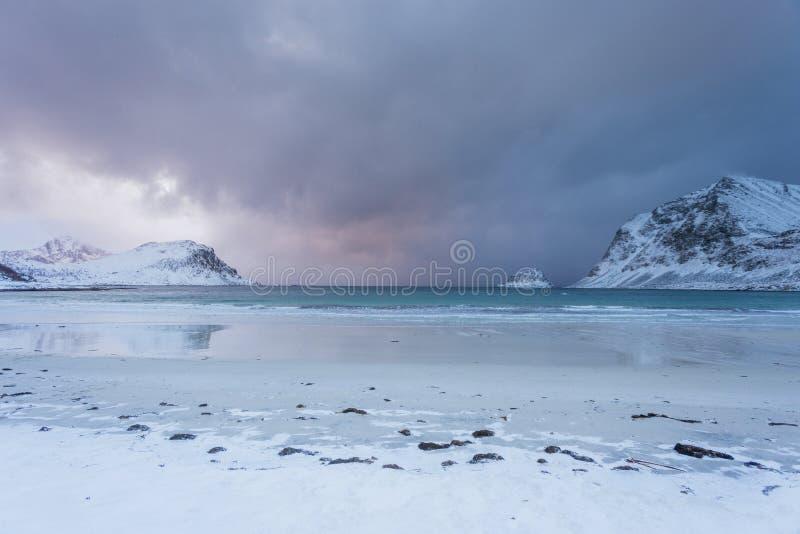 Spiaggia cristallina di inverno con le montagne nei precedenti, bella alba con neve in Norvegia fotografie stock