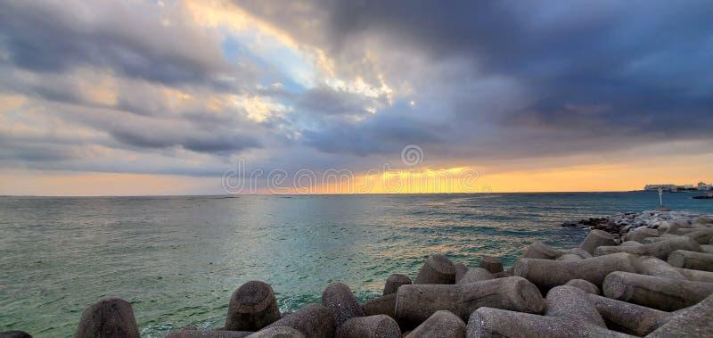 Spiaggia del tramonto a Okinawa in Giappone, con litorale roccioso e cieli nuvolosi immagini stock