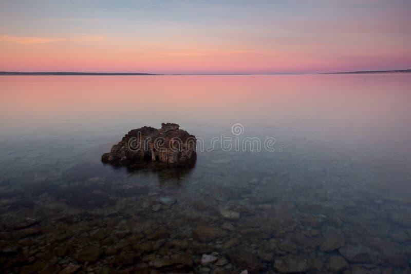 Spiaggia della Croazia di alba con il cielo di colore pastello e roccia in priorità alta fotografia stock libera da diritti