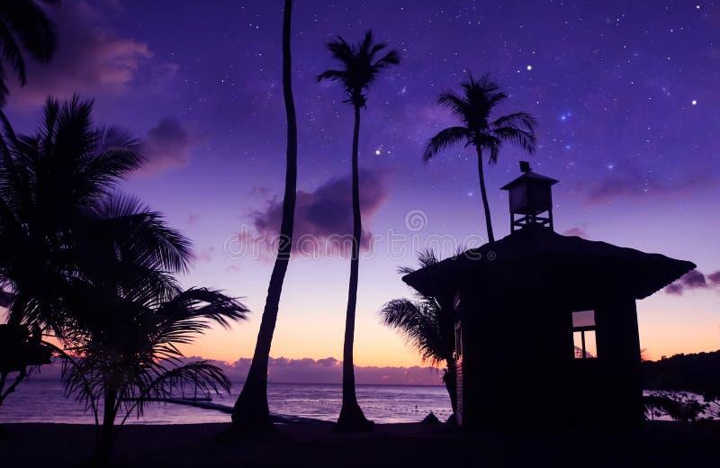 Spiaggia della noce di cocco con milione stelle e primi mattini di alba Condizione asiatica dell'uomo vicino alla piccola capanna fotografia stock