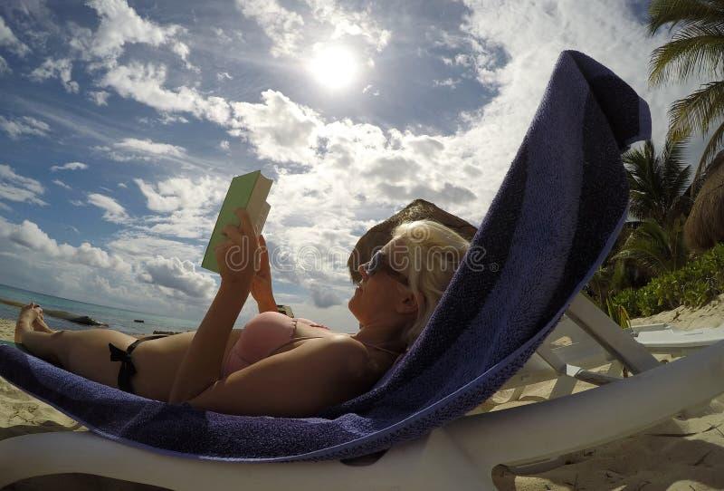 Spiaggia della ragazza del Messico che raffredda la palma colta del sole del libro immagini stock libere da diritti