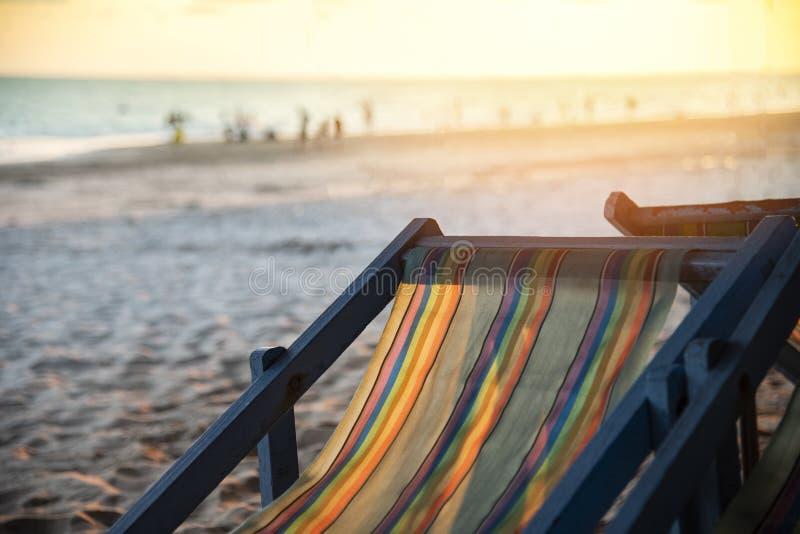 Spiaggia della sedia con il tramonto sulla vacanza del mare della spiaggia sabbiosa di estate fotografie stock