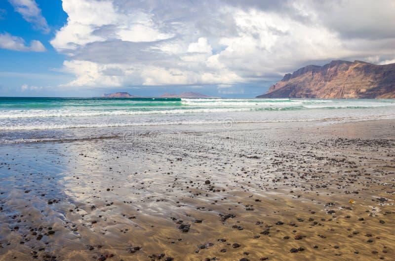 Spiaggia di Famara a bassa marea con le isole dell'arcipelago Chinijo nel fondo fotografia stock libera da diritti
