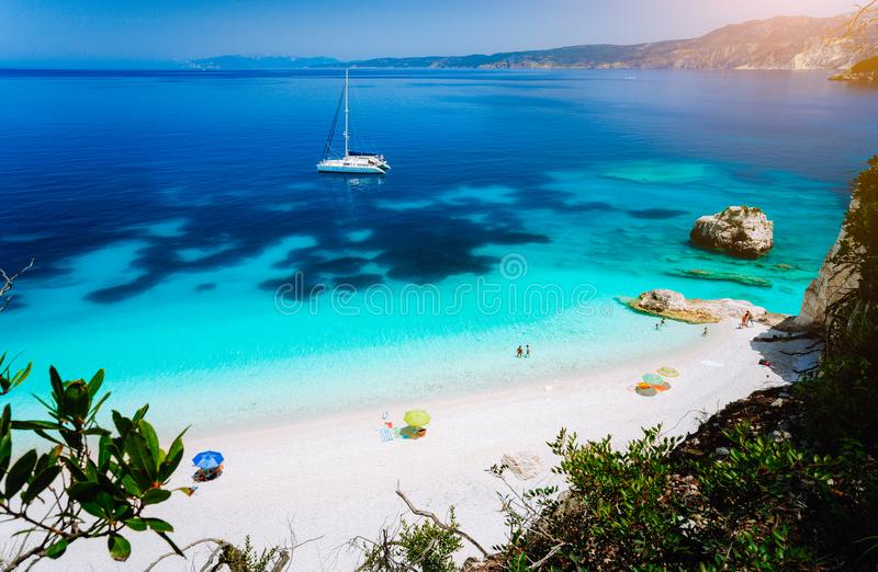Spiaggia di Fteri, Cephalonia Kefalonia, Grecia Yacht bianco del catamarano in chiara acqua di mare blu Turisti sulla spiaggia sa fotografie stock libere da diritti