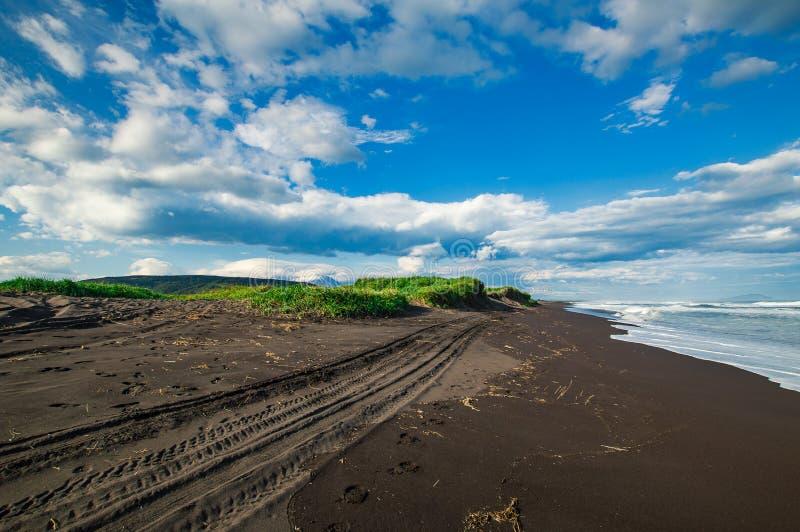 Spiaggia di Halaktyr kamchatka Federazione Russa Spiaggia di sabbia quasi nera di colore di buio dell'oceano Pacifico Montagne di fotografie stock
