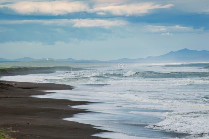 Spiaggia di Halaktyr kamchatka Federazione Russa Spiaggia di sabbia quasi nera di colore di buio dell'oceano Pacifico Montagne di fotografia stock libera da diritti