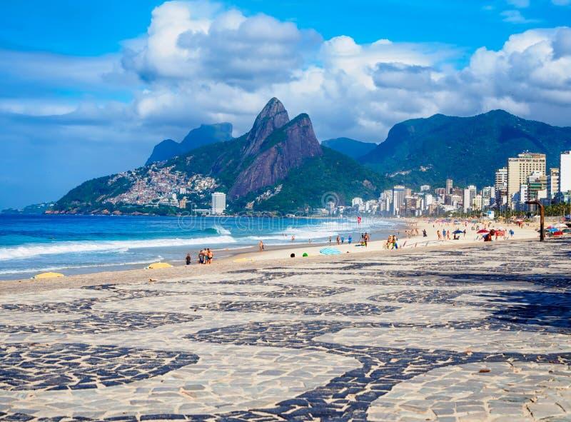Spiaggia di Ipanema con il mosaico del fratello di Dois Irmao due della montagna e del marciapiede in Rio de Janeiro immagine stock libera da diritti