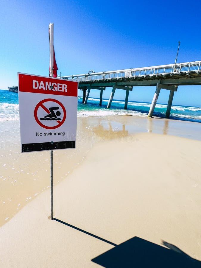 Spiaggia di nuoto del segno del pericolo, bandiera rossa fotografia stock