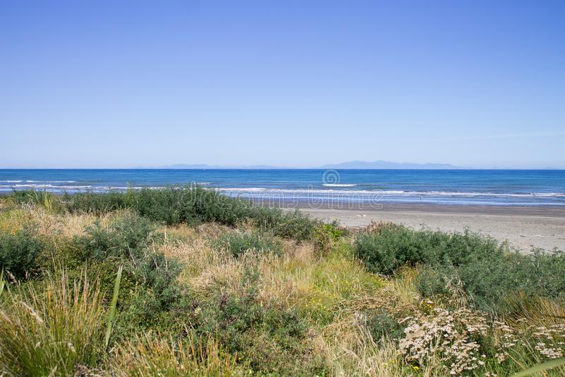 Spiaggia di Paraparaumu in Kapiti, Wellington, guardante fuori attraverso il mare di Tasman all'isola del sud della Nuova Zelanda immagine stock