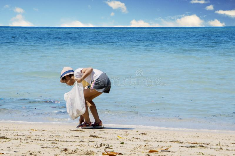 Spiaggia di pulizia della bambina immagine stock