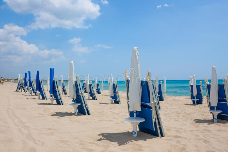 Spiaggia di sabbia con le chaise-lounge blu del sole nel giorno di estate immagini stock