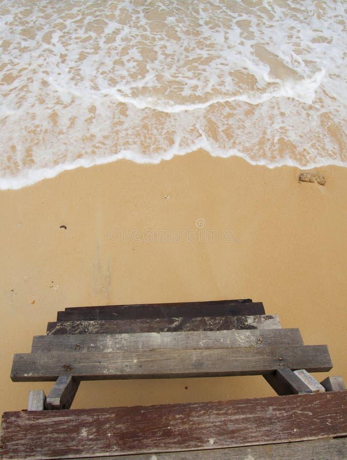Spiaggia di sabbia, onda e scala di legno fotografia stock