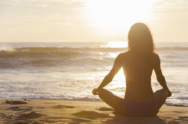 Spiaggia di seduta del bikini di tramonto di alba della ragazza della donna immagini stock