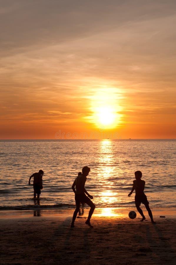 Spiaggia di tramonto con giocar a calcioe dei bambini fotografia stock